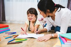 Child kid girl kindergarten drawing teacher education mother mom. With beautiful mother at interior room home royalty free stock photography