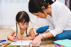 Child kid girl kindergarten drawing teacher education mother mom. With beautiful mother at interior room home stock photo
