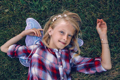 Child kid girl with long hair wearing pink fairy wings and plaid shirt, lying on grass Stock Photos