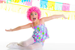 Child kid girl with party clown pink wig funny expression. Child kid girl with party clown pink wig funny happy open arms expression and garlands Royalty Free Stock Photo
