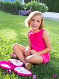 Child kid girl playing with makeup set sitting in grass Royalty Free Stock Photos
