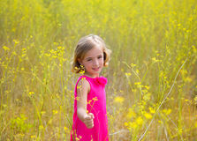 Child kid girl in spring yellow flowers field and pink dress Stock Images
