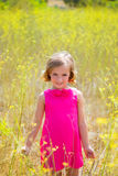 Child kid girl in spring yellow flowers field and pink dress. In Mediterranean forest Stock Images