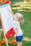 Child kid girl standing outside in summer autumn park drawing on easel with markers looking away playing studying. White Caucasian toddler child kid girl royalty free stock photography