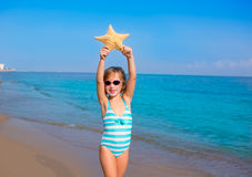 Child kid girl in summer beach vacations with starfish. And aqua sea royalty free stock photos