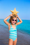 Child kid girl in summer beach vacations with starfish. And aqua sea stock image