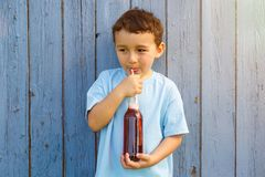 Child kid little boy drinking cola lemonade drink copyspace copy. Space outdoor outdoors outside bottle royalty free stock photography