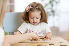 Child kid playing with puzzle shapes on low table in children room in nursery or preschool. stock image