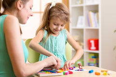 Child kid and woman play colorful clay toy at Royalty Free Stock Photos