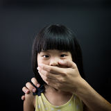 Child kidnap. Asian child being kidnapped, with mouth covered by an adult hand Royalty Free Stock Photo