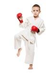 Child in kimono training karate. Martial art sport - boy in white kimono training karate punch or kick Royalty Free Stock Photo