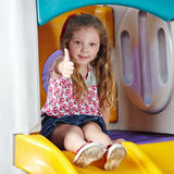 Child in kindergarten holding. Happy child in kindergarten holding her thumbs up Royalty Free Stock Image