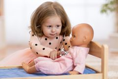 Child in kindergarten. Kid in nursery school. Little girl preschooler playing doctor with doll. stock photography