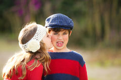 Child kiss. Little girl child giving kiss to young embarrassed boy Royalty Free Stock Photos