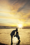 Child kiss her mother at coast. Silhouette little girl kissing her mother while holding hands and standing on the beach at sunset time Royalty Free Stock Images