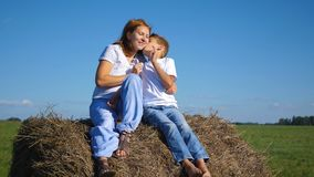 The child kisses his mother. On the haystack Stock Photos