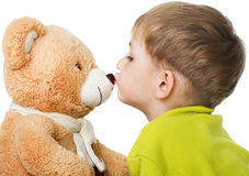 Child kisses teddy bear Royalty Free Stock Images