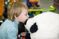 The child kisses a toy. The child kisses a soft toy of a bear on a profile against other toys stock photos