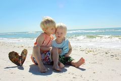 Child Kissing Brother on Beach. A young child is hugging and kissing his baby brother as they sit on the white sand beach by the ocean Stock Photos