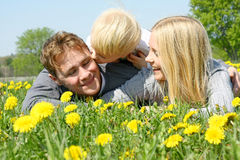 Child Kissing Father and Mother in Flower Meadow Royalty Free Stock Images