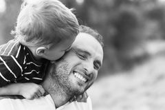 Child kissing father. Child playing with his father. Child kissing father. Daddy playing active games with his son outside. Happy family portrait. Laughing dad Stock Photography