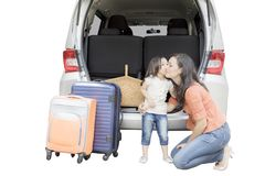 Child kissing her mother near their car. Image of little girl ready to holiday travel while kissing her mother near their car, isolated on white background Stock Images