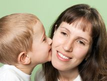 Child kissing mother. Child kissing smiling mother - family happiness Stock Photography