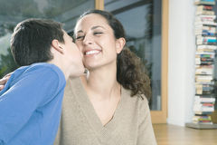 Child kissing mother. Young son kissing his mother on the ckeek Royalty Free Stock Photography