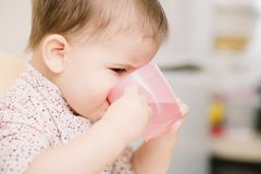 Child in the kitchen drinking from a cup of water stock photos