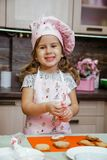 Child kitchen girls cook apron cupcake cookies small funny three sisters cap cream cream decor royalty free stock photo