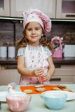 Child kitchen girls cook apron cupcake cookies small funny three sisters cap cream cream decor stock photography
