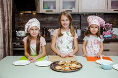 Child kitchen girls cook apron cupcake cookies small funny three sisters cap cream cream decor royalty free stock photos