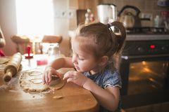 Child in the kitchen makes homemade cookies. kid cook at home. girl cuts hearts with a cutter royalty free stock photos