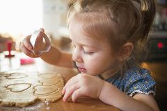 Child in the kitchen makes homemade cookies. kid cook at home. girl cuts hearts with a cutter stock images