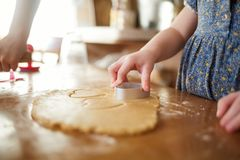 Child in the kitchen makes homemade cookies. kid cook at home. girl cuts hearts with a cutter stock photography