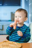The child in the kitchen with sausage. The child is sitting in the kitchen and greedily eats sausage Royalty Free Stock Photos