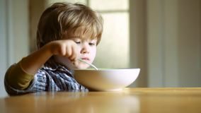 The child in the kitchen at the table eating. Little boy having breakfast in the kitchen. Happy baby boy spoon eats stock footage