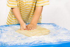 Child knead the dough by hand for making a cake Stock Photos