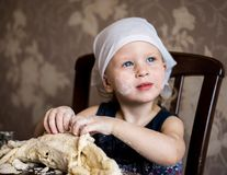 Child knead the dough in a kerchief Royalty Free Stock Photography