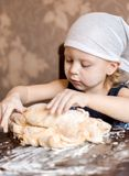 Child knead the dough in a kerchief Stock Image