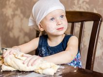 Child knead the dough in a kerchief Royalty Free Stock Photo