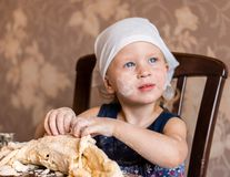 Child knead the dough in a kerchief Royalty Free Stock Images