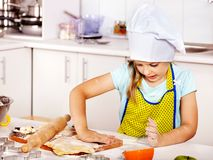 Child knead dough at kitchen. Royalty Free Stock Image