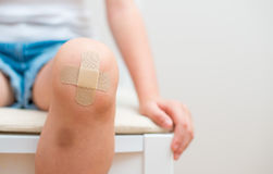 Child knee with adhesive bandage. Child knee with an adhesive bandage and bruise stock images