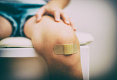 Child knee with an adhesive bandage. Royalty Free Stock Photo