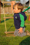 Child on knees. Young child kneeling on grass on a playground, in front of a rope ladder Royalty Free Stock Photography