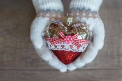 A child in knitted mittens is holding a glass Christmas heart. Christmas Stock Images