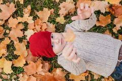 Baby lying on the grass and maple leaves, autumn royalty free stock photography