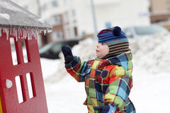 Child knocks icicles Stock Photos