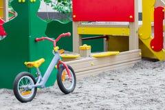 Child& x27; la bicicletta di s sta stando sulla sabbia ad un campo da giuoco fotografia stock